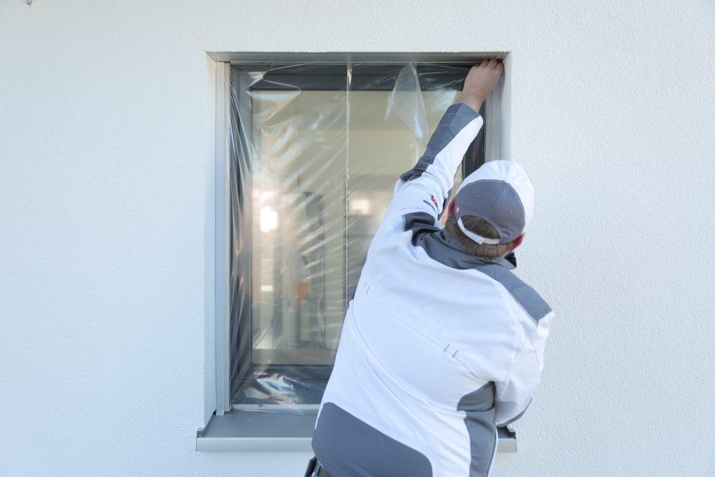 Ein Maler klebt mit Folie von Klauss-Klebeband ein kleines Fenster ab